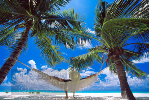 Maldives, man sitting in hammock on the beach, rear view