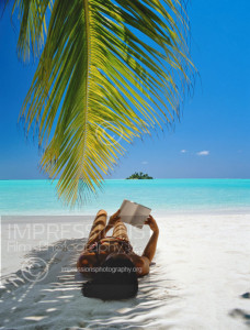 Maldives, woman lying under shade of palm tree on beach, reading book