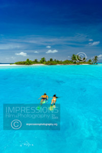 Tropical island and couple snorkelling in the Maldives, Indian Ocean, Asia - stock photo