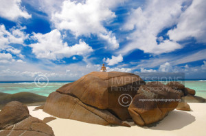 Young woman meditating on rock at the beach, Seychelles