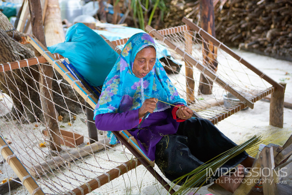 Lady in a joali preparing coconut leaves for ropes making on a Maldives local island