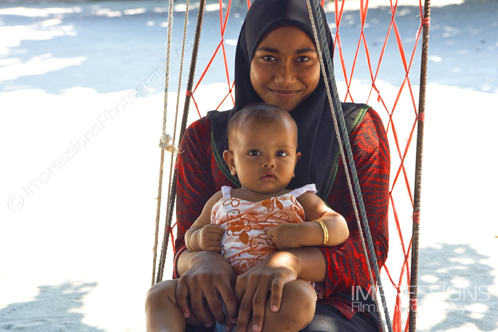 photo of a smiling mother and her young baby girl in a joali on a Maldives local island
