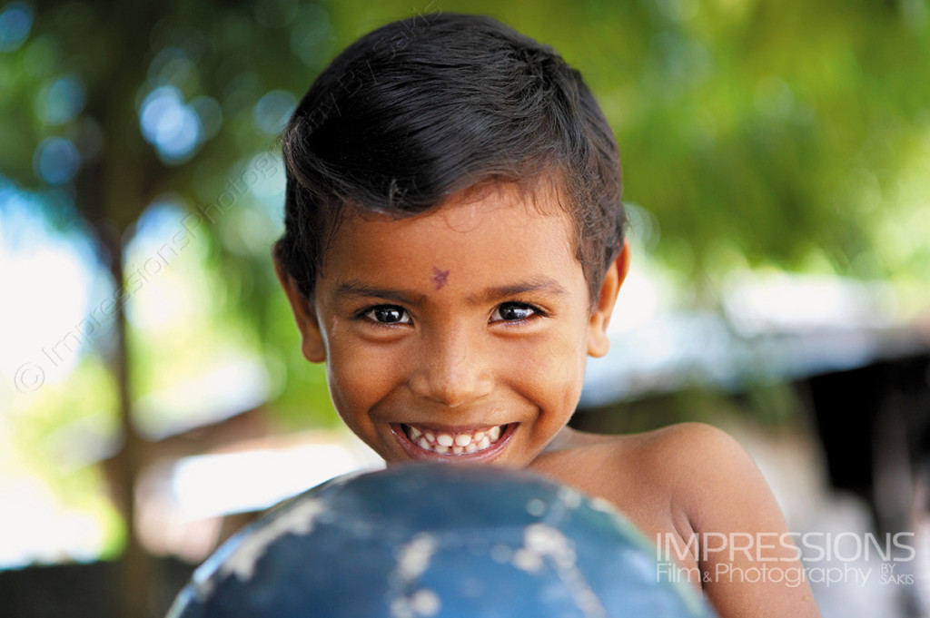 portrait of a young boy with a football ball on Maldives local island - photos of the people of Maldives series