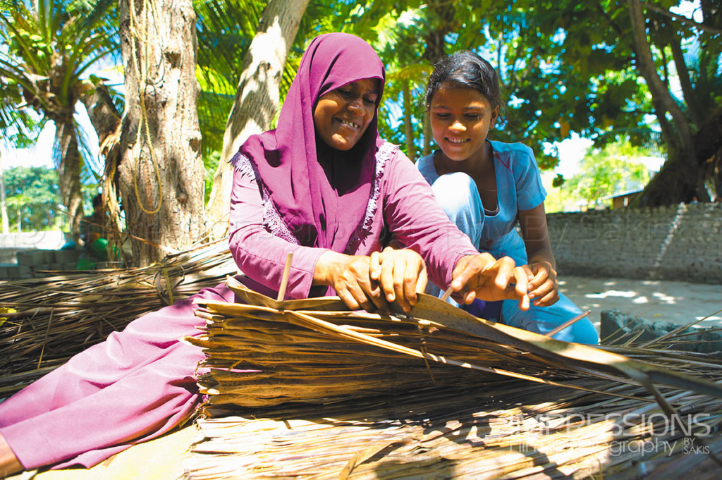 Maldives traditions a mother and daughter weaving coconut palms for kajan roofing