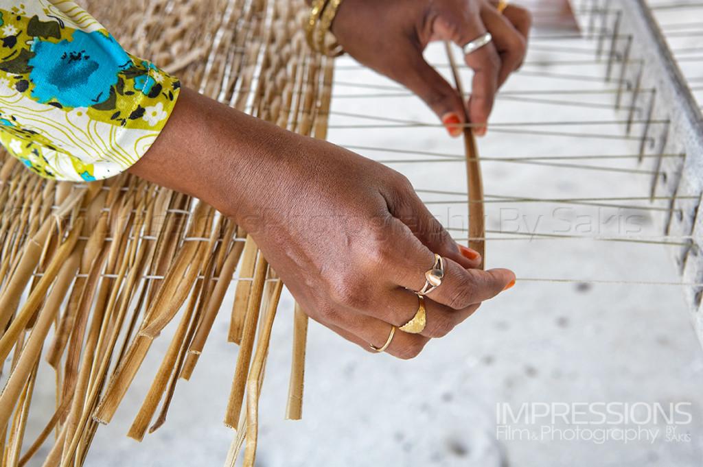 Maldives tradition hands of a Maldivian woman weaving Coconut leaves to make mats called Kunaa.